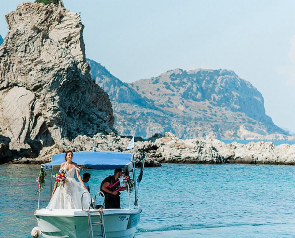 bride arriving on a boat for her destination wedding in Halki by eventions wedding planners