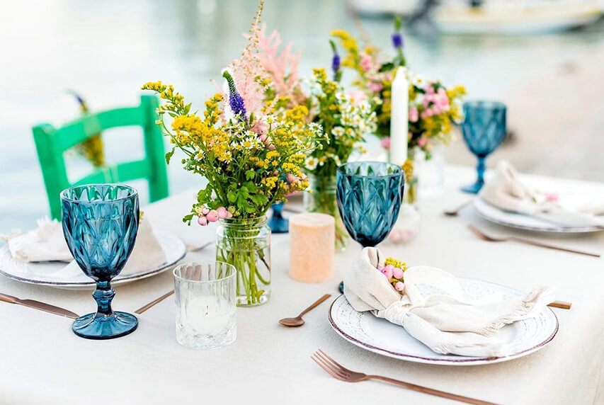 Minimal and Mediterranean wedding table setting with yellow flowers, and blue shades for a destination wedding in greece by eventions wedding planners