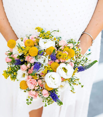 minimal wedding bouquet with yellow flowers, purple flower and white roses for a destination wedding in Greece