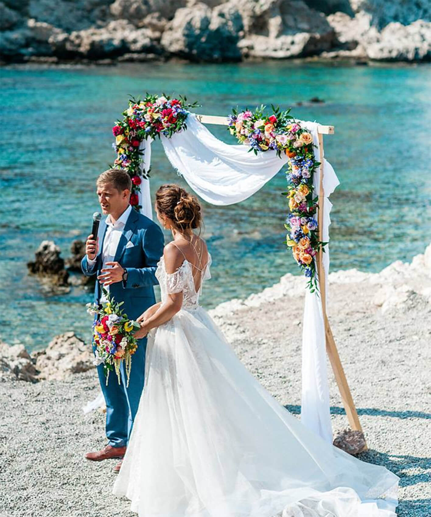 Destination wedding in Greece by the sea with colourful details and a flower wedding arch
