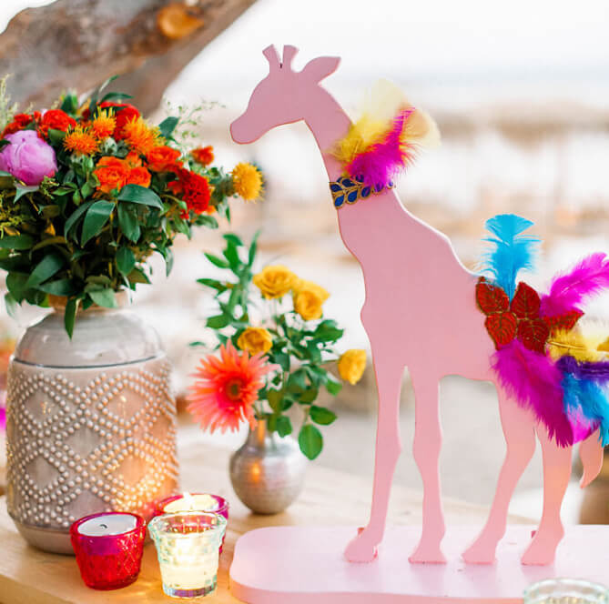 colourful baptism decor in greece with pink giraffes and feathers
